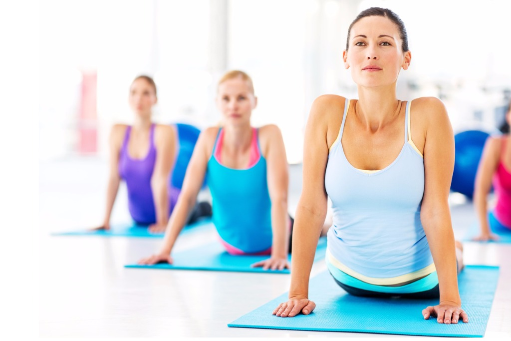 instructor-and-customers-practicing-yoga-exercise-in-gym-picture-id471840221.jpg