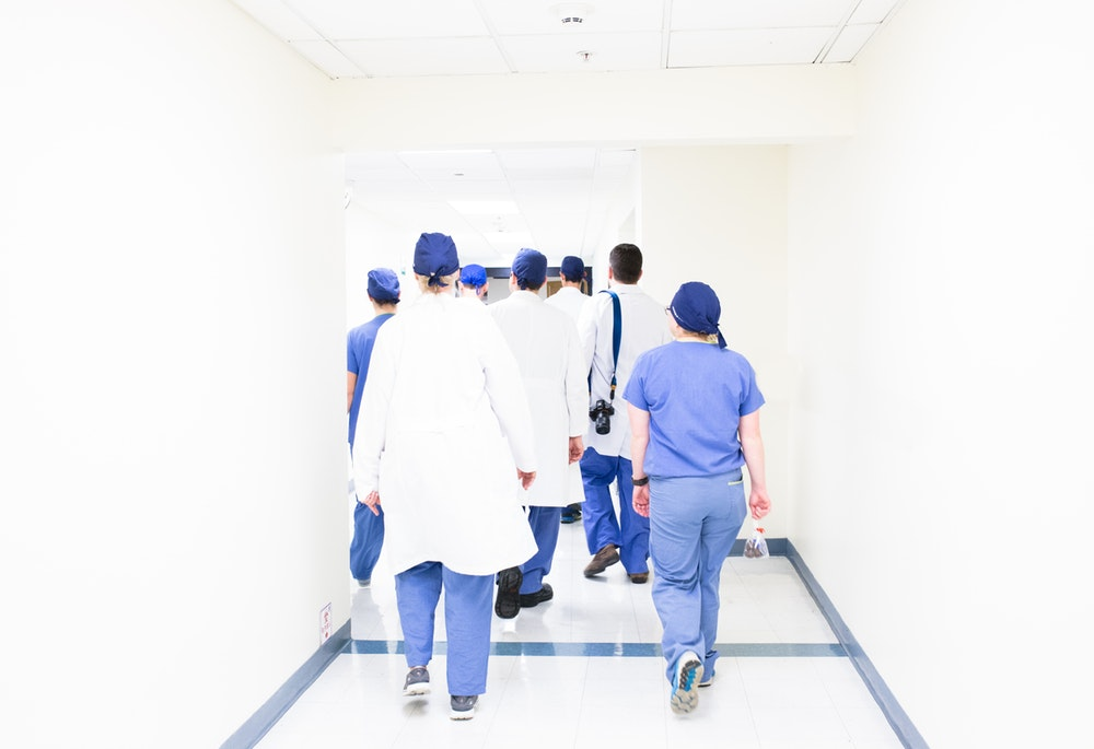 group of doctors walking on hospital hallway