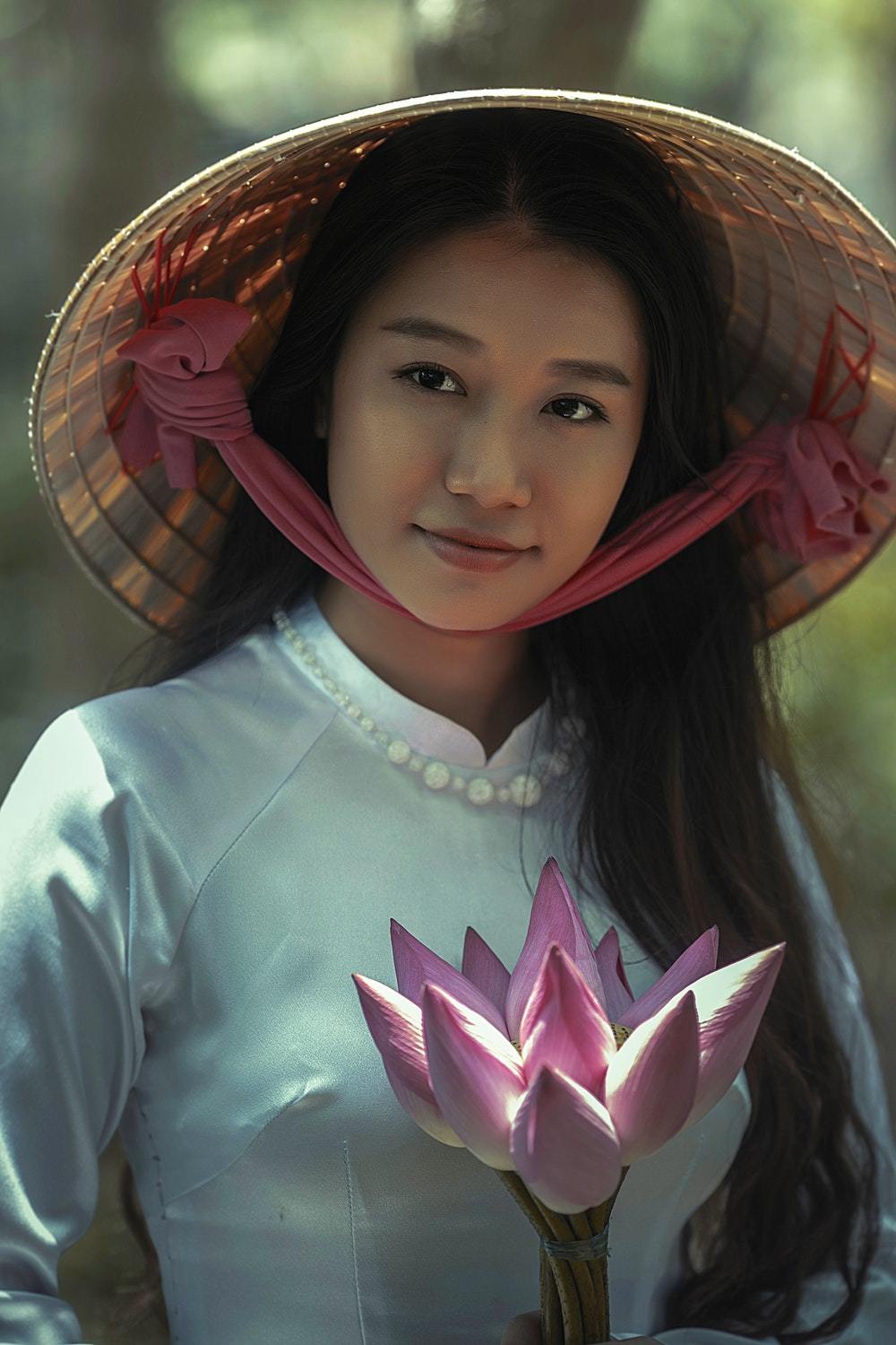 woman wearing white long-sleeved dress and brown sungat holding pink petaled flower