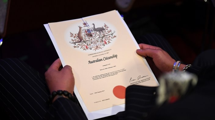 An Australian citizenship recipient holds his certificate during a citizenship ceremony on Australia Day in Brisbane, Thursday, Jan. 26, 2017. (AAP Image/Dan Peled) NO ARCHIVING