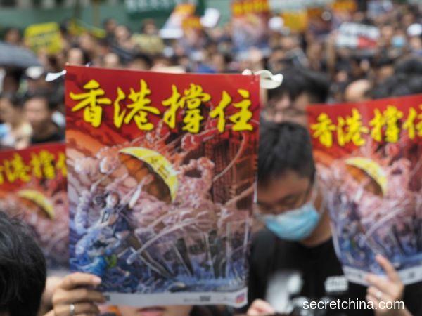 7月7日,23萬香港人參加了九龍「反送中」遊行,遊行人士手持《看中國》印刷的「香港撐住」畫報。