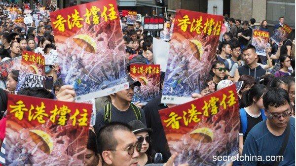 7月7日,23萬香港人參加了九龍「反送中」遊行,香港市民手持《看中國》印刷的「香港撐住」畫報。
