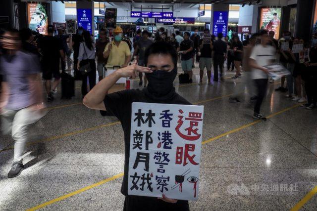 """一些示威者用黑布蒙眼,以此象征为被射中右眼的女子""""讨回眼睛""""。(图片:中央社)"""