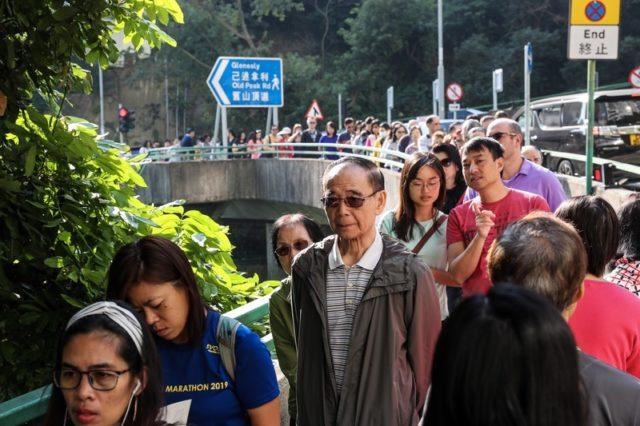 大量香港市民排在投票站外等待投票。(图片来源:中央社)