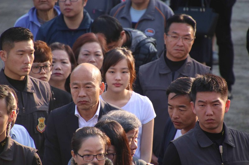 国民党总统候选人韩国瑜(前)跟女儿韩冰(后),一早就前往高雄市林园区的普愿寺投票所,在队伍中等待领票。(图片来源:中央社)