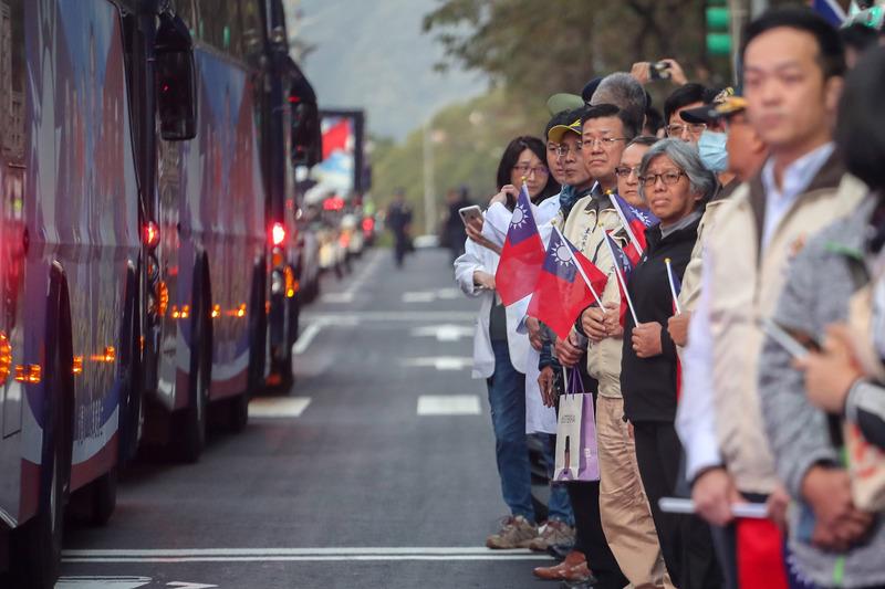不少民众自发停下脚步,手持国旗向车队致意,国军弟兄则向车队行军礼。(图片来源:中央社)